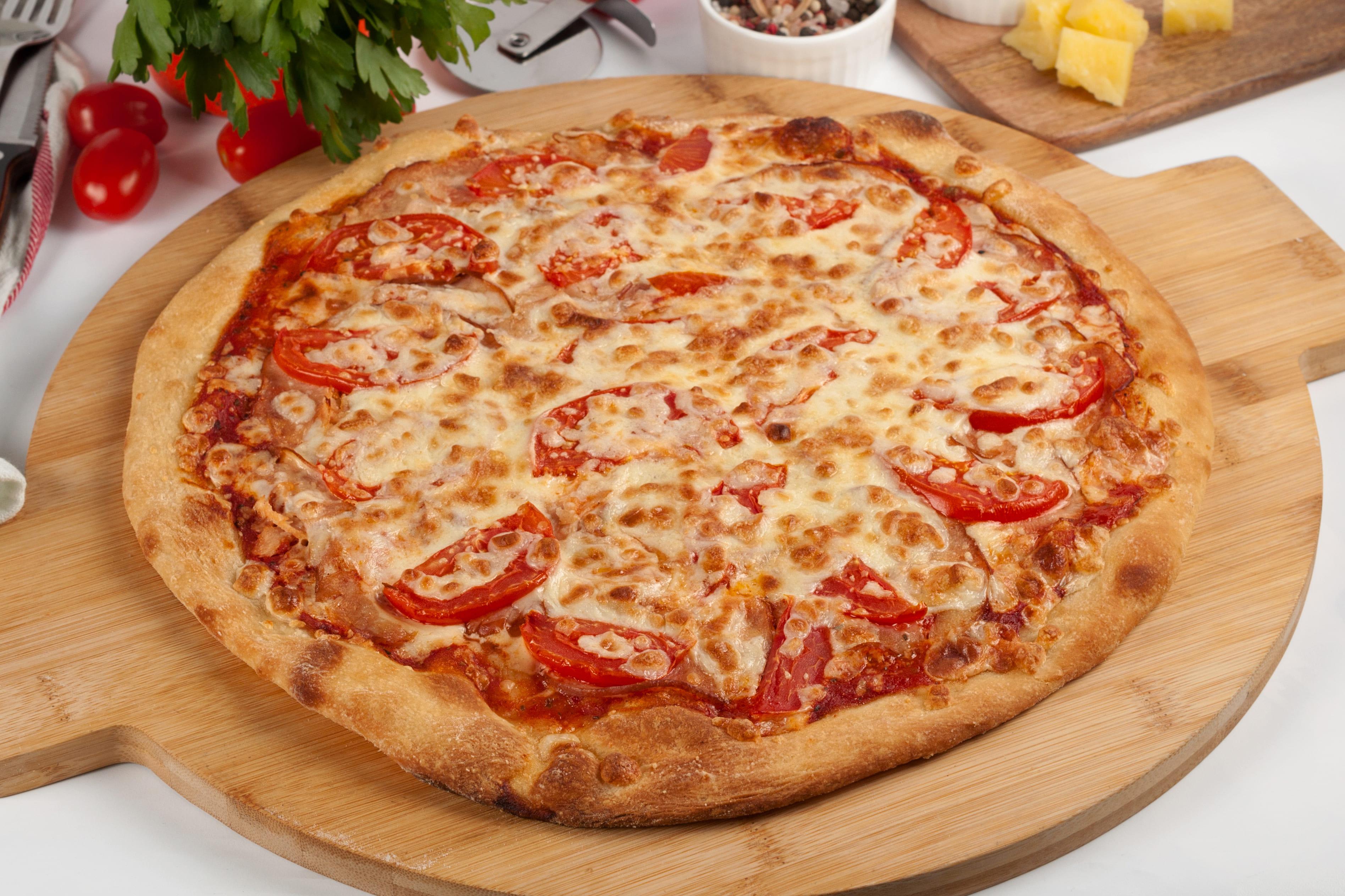 Пицца с ветчиной и томатами.